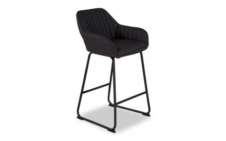 Angled shot of the Brooks dark grey faux leather barstool with long black metal legs