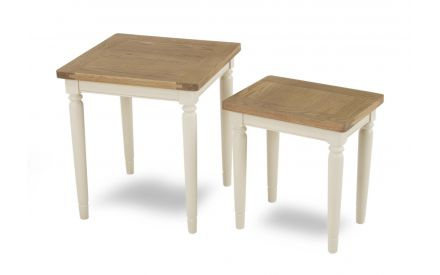A cream nest of 2 tables with oak top from EZ Living Furniture's Farmhouse range. Angled view.