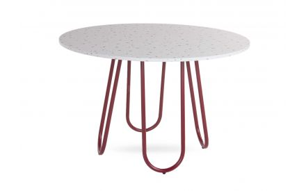 A round white speckled terrazo dining table top with red legs from EZ Living Furniture's Stulle range. Angled view of table