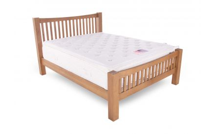A 6ft smokey oak bedframe from EZ Living's Barna range shown with a mattress. Angled view of slat foot & headboard.